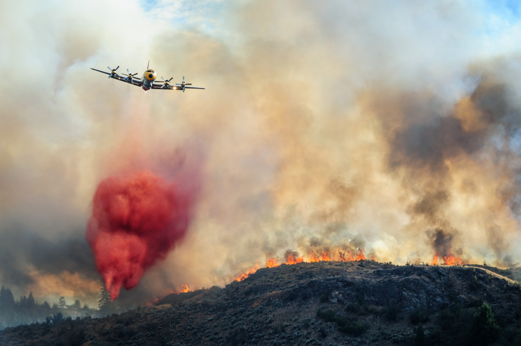 A bomber plane drops red fire retardant on flames that burned Monday evening through the sagebrush near Spotted Lake west of Osoyoos. (Richard McGuire photo)