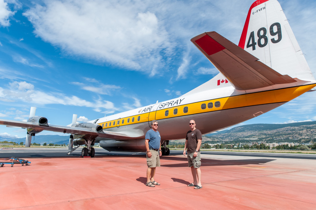 Ben Moerkoert (left) Air Attack officer, and Jeff Pulkinen, co-pilot, stand on the tarmac below an air tanker made from a converted Electra L188, a turboprop plane first introduced in 1957. The tarmac is red from spilled fire retardant. (Richard McGuire photo)