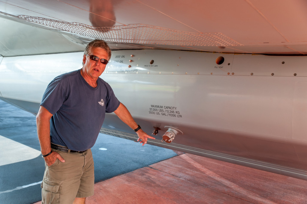 Ben Moerkoert, Air Attack officer, points to where a hose is connected to fill a tank with fire retardant. The tank can hold up to 3,000 U.S. gallons. Sometimes the plane is flown back to base after it drops its load so that more retardant can be added for another drop. (Richard McGuire photo)