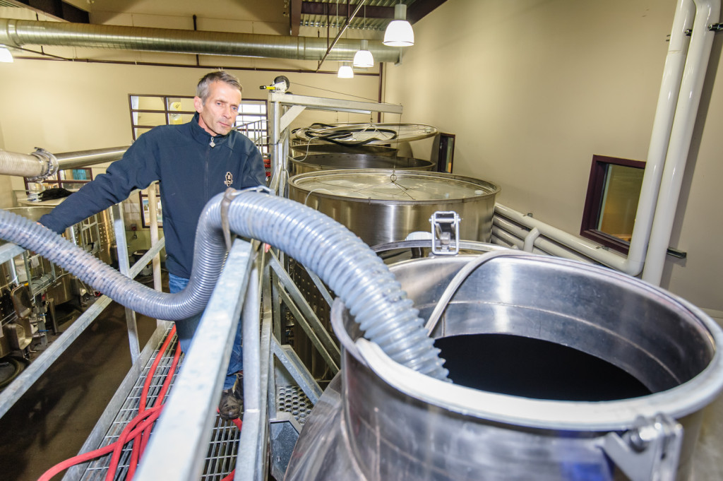 Randy Picton (left), winemaker at Nk'Mip Cellars, looks on as a hose empties fresh grape juice into a tall steel storage tank. (Richard McGuire photo)