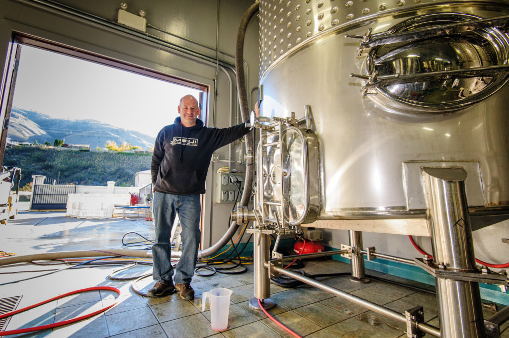 Winemaker Chris Tolley at Moon Curser Vineyards shows the giant tanks where juice from the grapes is collected prior to making wine. (Richard McGuire photo)