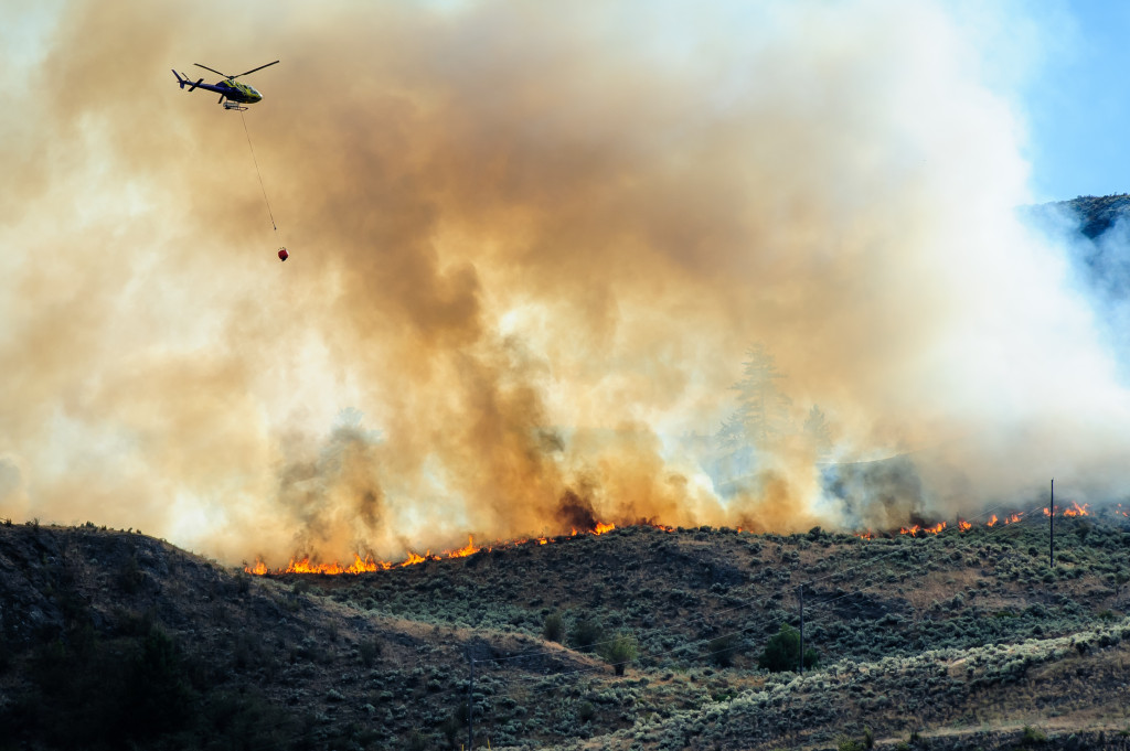 A helicopter prepares to drop water on a fire that burned through sagebrush near Spotted Lake west of Osoyoos on Aug. 19, 2013. (Richard McGuire photo)