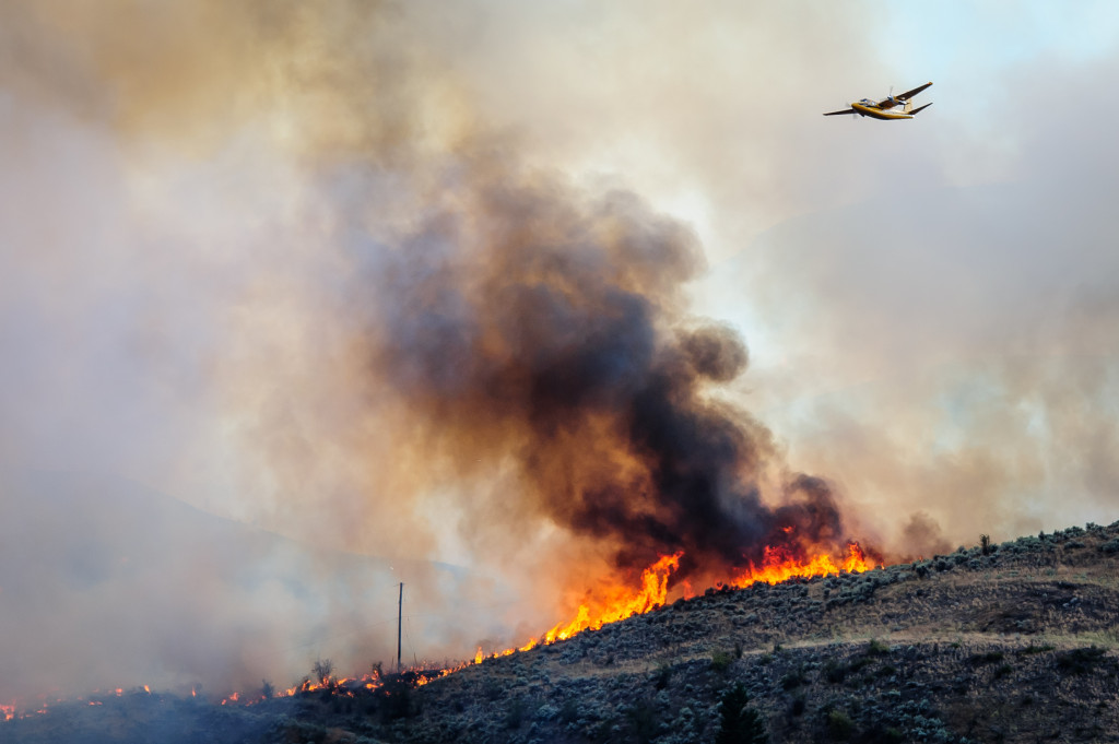 A bird dog plane flies above a fire marking the route for a bomber to follow. The fire was fanned by gusting winds as it spread through sagebrush near Spotted Lake west of Osoyoos on Aug. 19, 2013. The aerial attack on the fire is directed from the bird dog. (Richard McGuire photo)