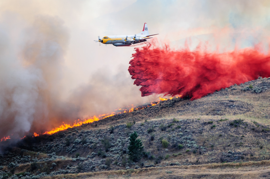 A bomber plane drops red fire retardant on a strip of land between approaching flames and a large house. With this one drop, it appeared to stop the flames from gaining on the house. The brush fire occurred Aug. 19, 2013 night near Spotted Lake west of Osoyoos. (Richard McGuire photo)